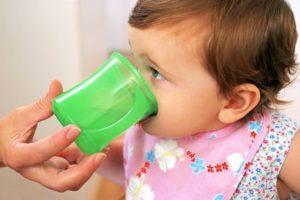 малыш пьет из чашки
